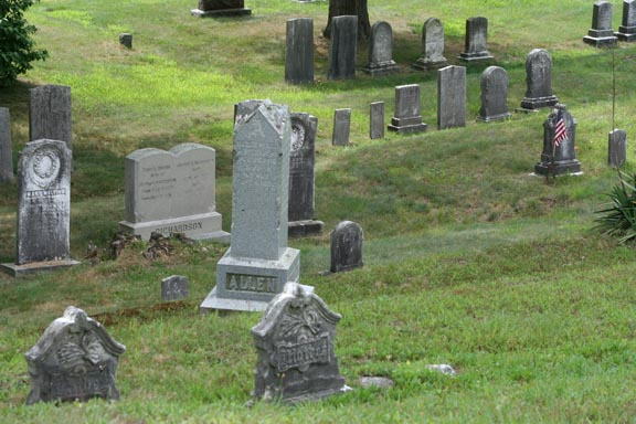 Looking down a hill at various types of headstones