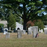 A group of headstones, note the house in back