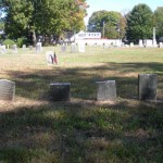 A small row of small headstones in front