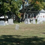 Headstones in the back, left side of the cemetery